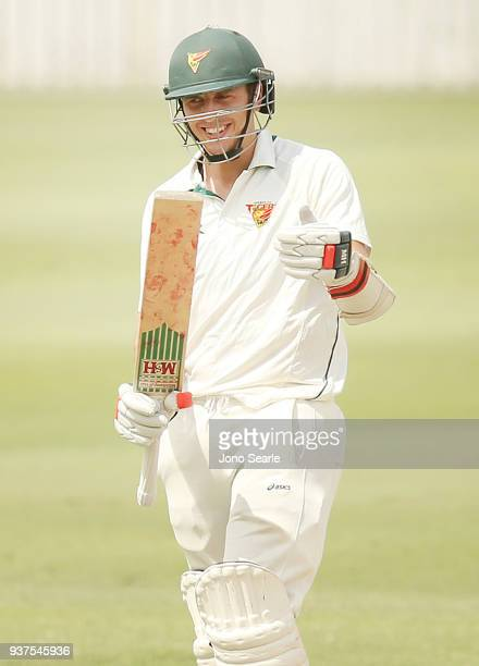 Tasmania player Sam Rainbird celebrates making 50 runs as Queensland player Jimmy Peirson looks on during day three of the Sheffield Shield final...