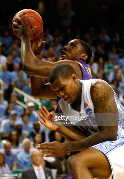 Tasmin Mitchell of the Louisiana State University Tigers drives against Deon Thompson of the North Carolina Tar Heels during the second round of the...