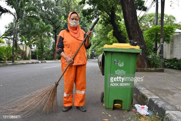 Tasriyah street sweeper, poses for a picture in Jakarta on April 20, 2020 during the COVID-19 coronavirus pandemic. - Ahead of May Day on May 1 AFP...
