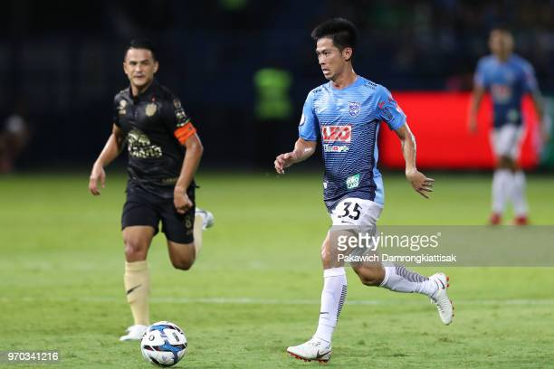 Tassanapong Mhuaddarak of Bangkok Glass FC goes past Suchao Nutnum of Buriram United FC during the Thai League 1 match between Bangkok Glass FC and...