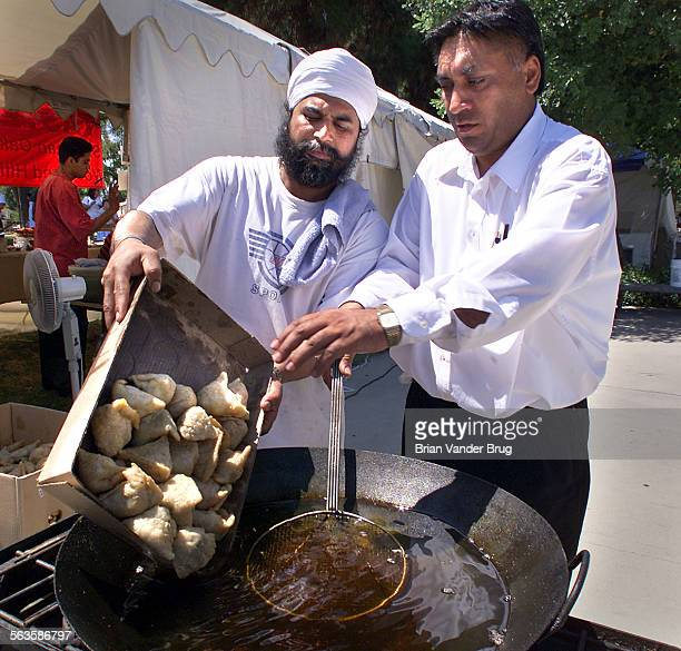 Taste of India restaurant owner Surinder Singh right helps chef Harbans Singh left pour a box of samosas into a wok of hot oil at the India...