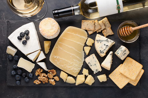Tasting cheese dish on a dark stone plate. Food for wine and romantic date, cheese delicatessen on a black concrete background. Top view 886381742