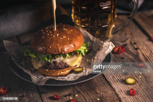 tasty burger and mug of beer on wooden table - burger stock pictures, royalty-free photos & images