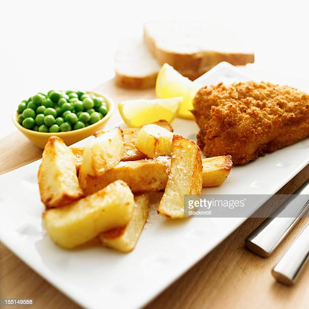 Tasty fish and chips with lemon, side peas.