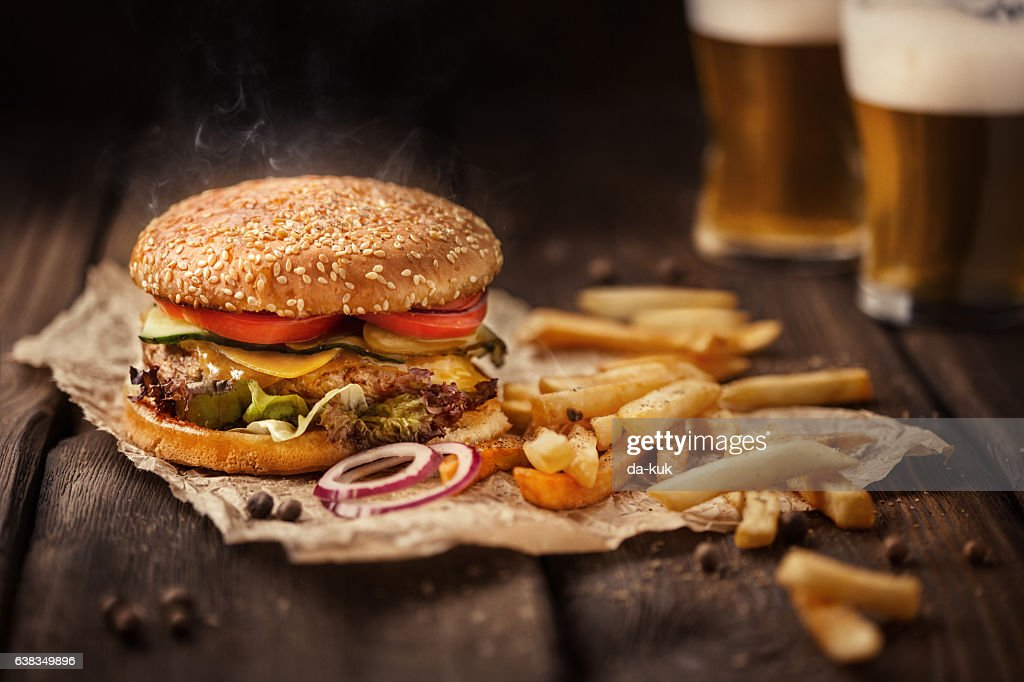 Tasty hamburger with french fries and beer on wooden table : Stock-Foto
