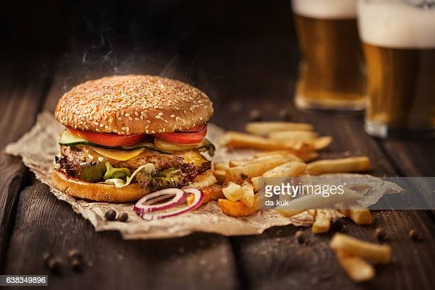 tasty hamburger with french fries and beer on wooden table - cheeseburger stock pictures, royalty-free photos & images