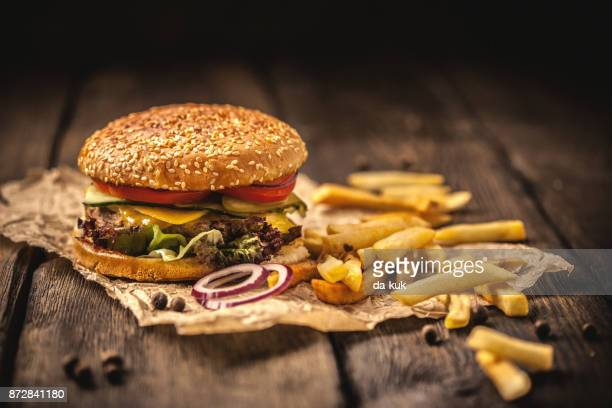 tasty hamburger with french fries on wooden table - hamburger stock pictures, royalty-free photos & images