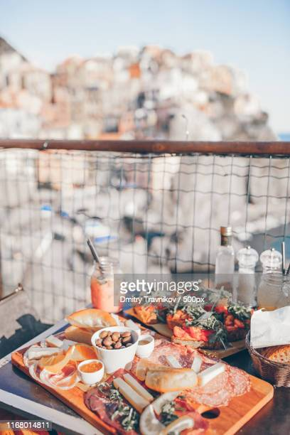 tasty italian snack fresh bruschettes, cheeses and meat on the board in outdoor cafe with - extra virgin olive oil stock pictures, royalty-free photos & images