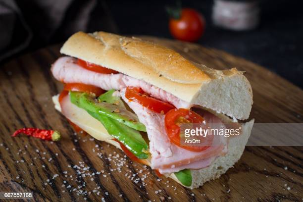 Tasty sandwich with avocado, ham, tomato and cheese