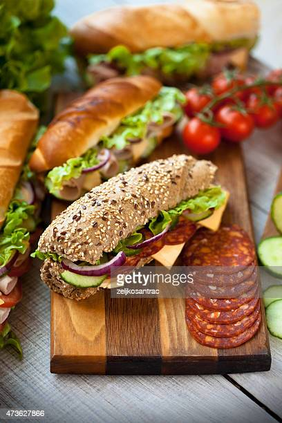 tasty sandwiches on a wooden table - submarine sandwich stock pictures, royalty-free photos & images