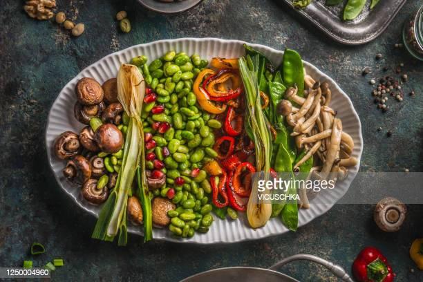 tasty vegan snack plate with roasted vegetables, edamame beans, mushrooms and red pomegranate seeds - prato de soja - fotografias e filmes do acervo