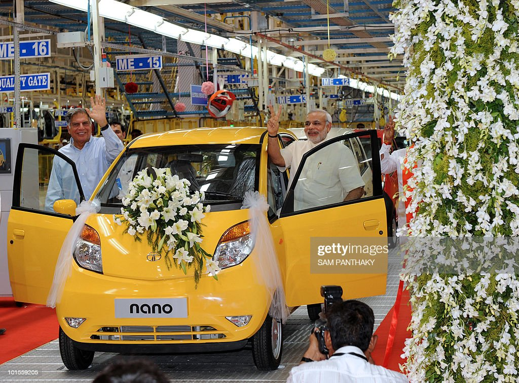 Tata Group chairman Ratan Tata (L) and Gujarat state Chief Minister Narendra Modi pose besides a Nano car during a rollout ceremony at the new Nano plant at Sanand, some 40 kms. from Ahmedabad, on June 2, 2010. The new Nano plant in Gujarat has the capacity to manufacture 250,000 units annually, and aims to increase production to 350,000. Just 13 per 1,000 people own a car in India, compared with 550 per 1,000 in Germany and 495 in France. AFP PHOTO/ Sam PANTHAKY