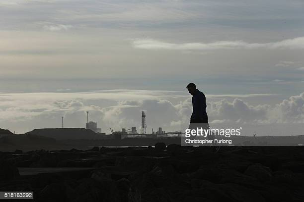 Tata steel worker contemplates his future on Aberavon beach in the shadow of the Tata Steel steel plant at Port Talbot on March 30, 2016 in Port...