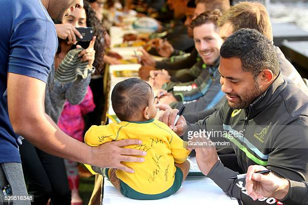 Tatafu PolotaNau of the Wallabies signs his autograph for a young fan during the Australian Wallabies Fan Day at The Crown Promenade River Walk on...