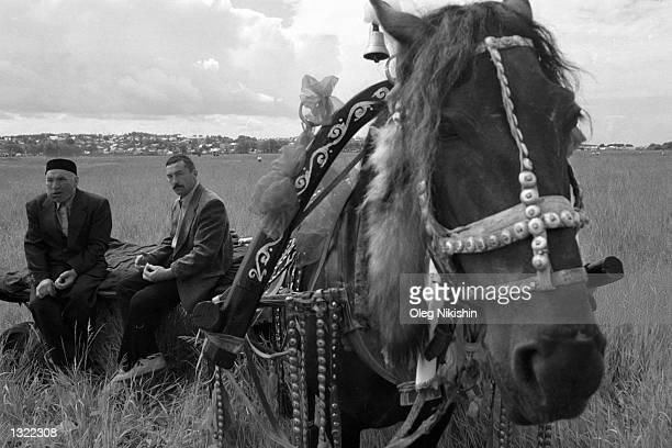 Tatar peasants rest near a horse cart on their way to a Sabantuy holiday festival June 9 2001 near Baltaci in the Tatarstan region of Russia Each...