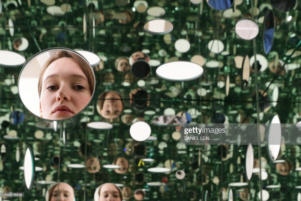 A Tate employee poses in front of 'The Passing Winter 2005' by Japanese artist Yayoi Kusama, in the new Switch House extension of the Tate Modern, in London on June 14, 2014. / AFP / Daniel Leal-Olivas / RESTRICTED