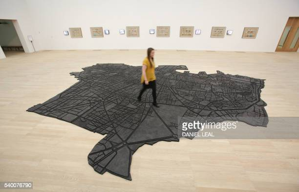 A Tate employee poses on top of 'Beirut Caoutchouc 20042008' by Marwan Rechmaoui an artwork on display in the new Switch House extension of the Tate...
