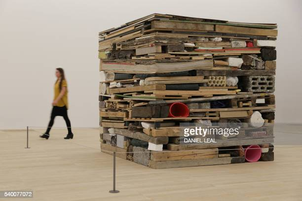 A Tate employee walks past the artwork 'Stack' 1975 by Tony Cragg in the new Switch House extension of the Tate Modern in London on June 14 2016 /...