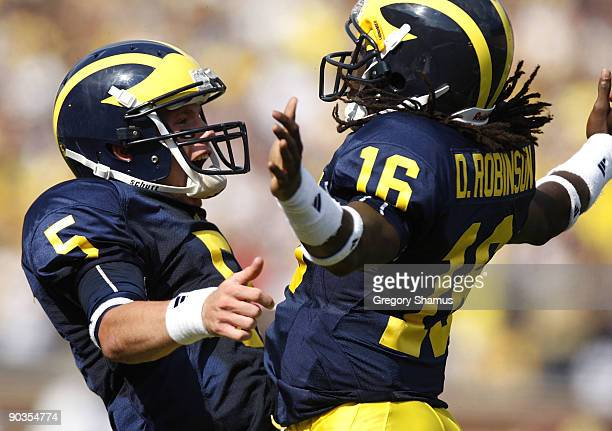 Tate Forcier of the Michigan Wolverines celebrates with Denard Robinson after Robinson ran for a long first quarter touchdown against the Western...