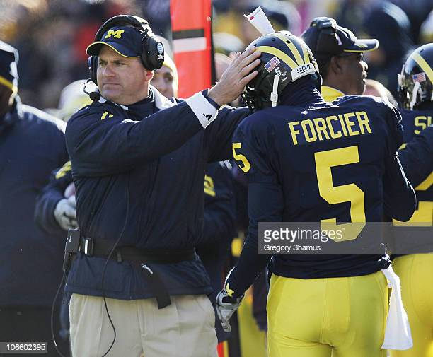 Tate Forcier of the Michigan Wolverines is congratulated by head coach Rich Rodriguez after scoring an overtime touchdown while playing the Illinios...