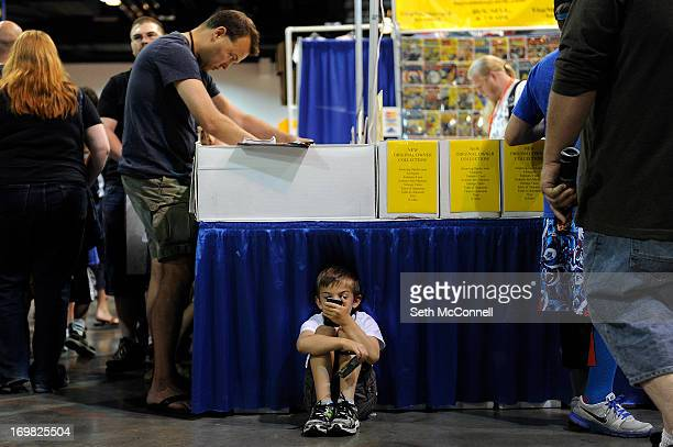 Tate ReederHolman plays a game of Tetris on a cell phone as his dad Dave Reeder browses through a box of comic books during Denver Comic Con at the...