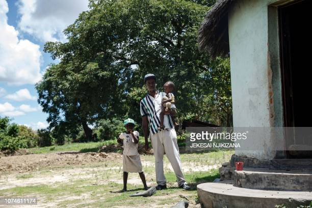 Tatenda Chingarambe a villager who works parttime as a labourer tilling neighbours' fields to earn an income to support his family stands by his...