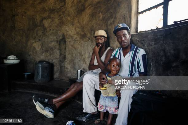 Tatenda Chingarambe a villager who works parttime as a labourer tilling neighbours' fields to earn an income to support his family holds his daughter...
