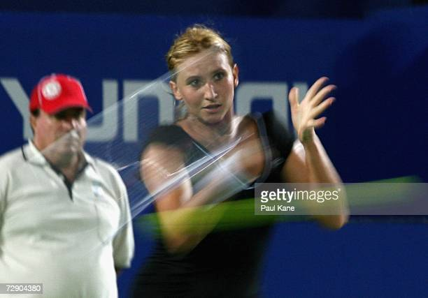 Tatiana Golovin of France plays a forehand shot to Ashley Harkleroad of the USA during the Hopman Cup Group A match between USA and France at...