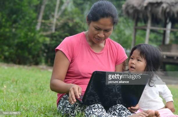Tatiana Gualinga sits with her niece Yulexi looking at a laptop on a grass pitch of the village Sarayaku Ecuador 27 October 2016 The indigenous...