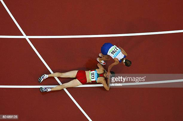 Tatiana Sibileva of Russia helps up Ryta Turava of Belarus from the track after the Women's 20km Walk Final held at the National Stadium during Day...