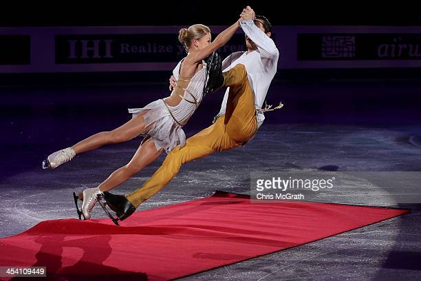 Tatiana Volosozhar and Maxim Trankov of Russia fall after skating into the red carpet on their entrance for the Pairs Free Skating Final victory...