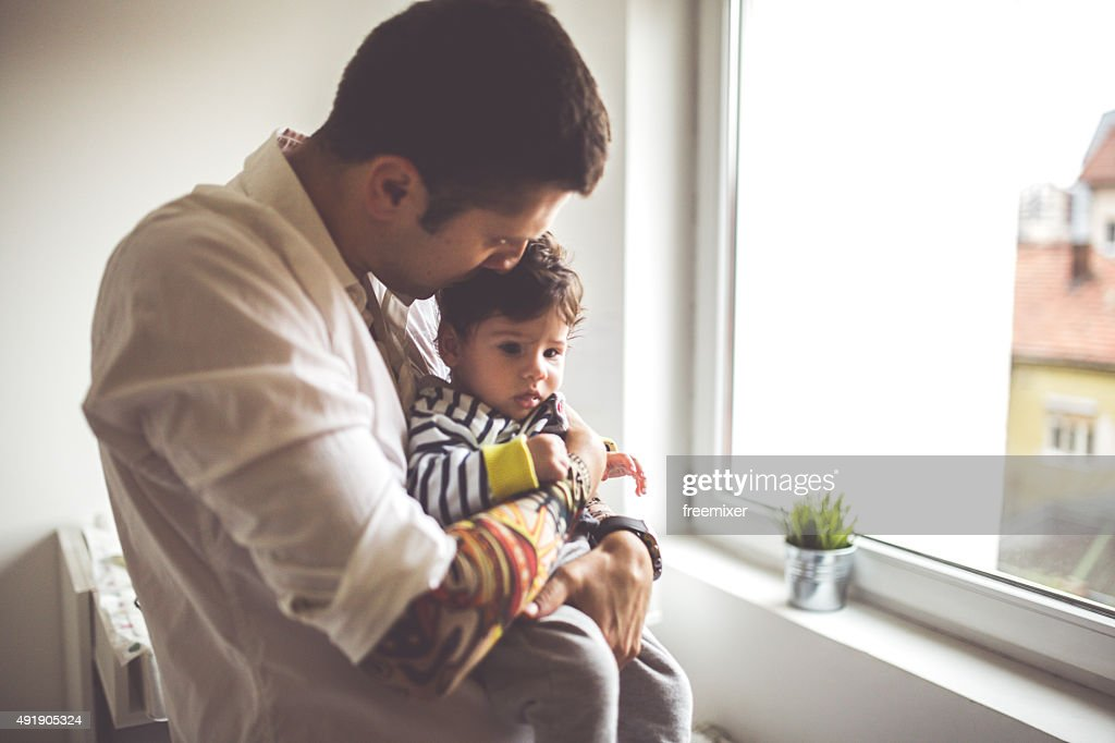 Tatooed father gazing at newborn son : Stock Photo