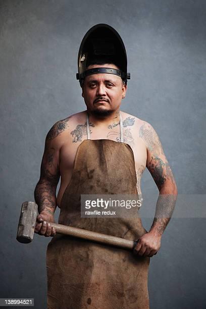 Tatooed iron worker holding a hammer.