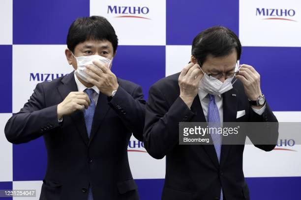 Tatsufumi Sakai, president and chief executive officer of Mizuho Financial Group Inc. , right, and Masahiko Kato, incoming president and chief...