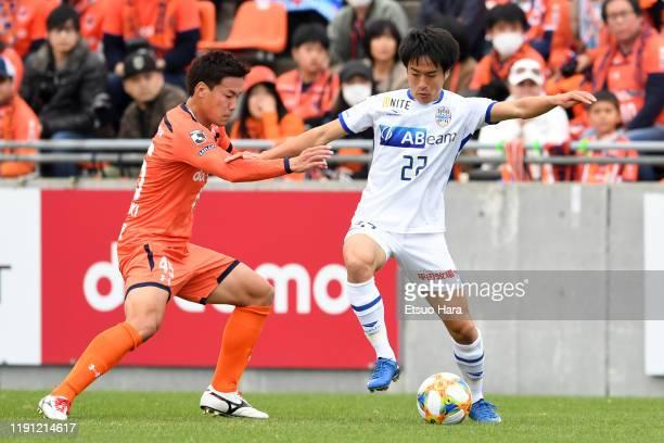Tatsuhiro Sakamoto of Montedio Yamagata and Kazushi Kushibiki of Omiya Ardija compete for the ball during the J.League J1/J2 Play-Off first round...