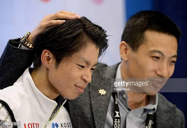 Tatsuki Machida of Japan reacts after his skate with coach Anthony Liu of Australia during the men's short program at Skate America 2013 at Joe Louis...