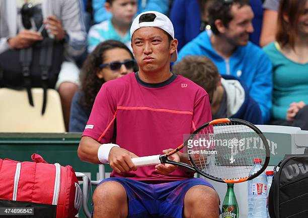 Tatsuma Ito of Japan looks on during a break in play in his Men's Singles match against Fabio Fognini of Italy on day two of the 2015 French Open at...