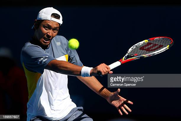 Tatsuma Ito of Japan plays a backhand in his second round match against Marcos Baghdatis of Cyprus during day three of the 2013 Australian Open at...