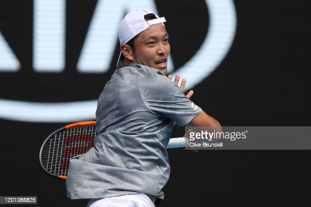 Tatsuma Ito of Japan plays a shot during his Men's Singles second round match against Novak Djokovic of Serbia on day three of the 2020 Australian...
