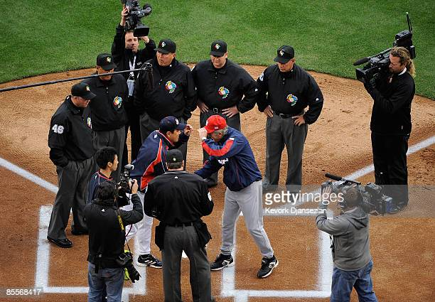 Tatsunori Hara of Japan and Manager Davey Johnson of the United States meet with officials before the semifinal game of the 2009 World Baseball...