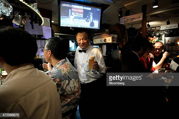 Tatsuo Aoki jointowner of Bakusyu Club Popeye bar and chairman of the Japan Craft Beer Support Group carries a glass of craft beer for a customer...