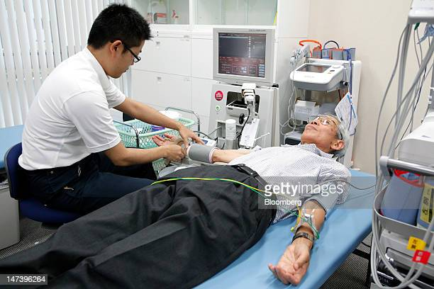 Tatsuo Muto right, undergoes a flow-mediated dilation examination during a demonstration at the University of Tokyo's Kashiwa campus in Kashiwa City,...