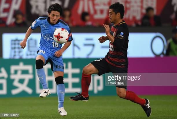 Tatsuya Hasegawa of Kawasaki Frontale and Mitsuo Ogasawara of Kashima Antlers compete for the ball during the J.League J1 match between Kashima...