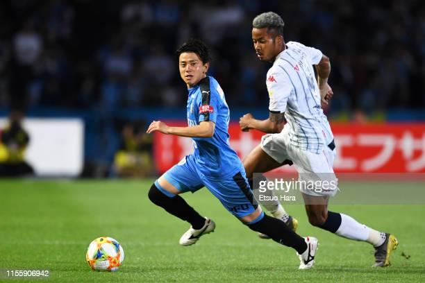 Tatsuya Hasegawa of Kawasaki Frontale and Musashi Suzuki of Consadole Sapporo compete for the ball during the J.League J1 match between Kawasaki...
