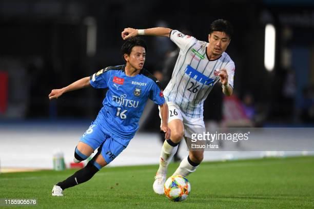 Tatsuya Hasegawa of Kawasaki Frontale and Ryota Hayasaka of Consadole Sapporo compete for the ball during the J.League J1 match between Kawasaki...