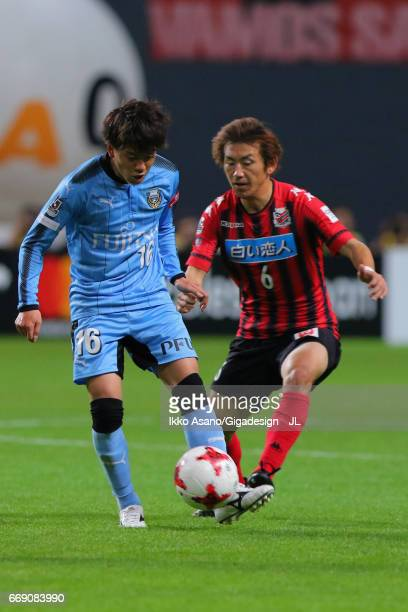 Tatsuya Hasegawa of Kawasaki Frontale controls the ball under pressure of Shingo Hyodo of Consadole Sapporo during the J.League J1 match between...