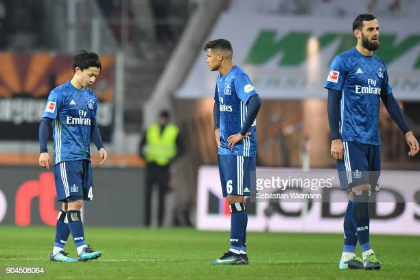 Tatsuya Ito Douglas Santos and Mergim Mavraj of Hamburg stand on the pitch after the Bundesliga match between FC Augsburg and Hamburger SV at...