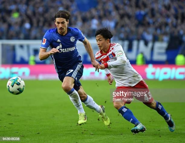 Tatsuya Ito of Hamburg is challenged by Benjamin Stambouli of Schalke during the Bundesliga match between Hamburger SV and FC Schalke 04 at...