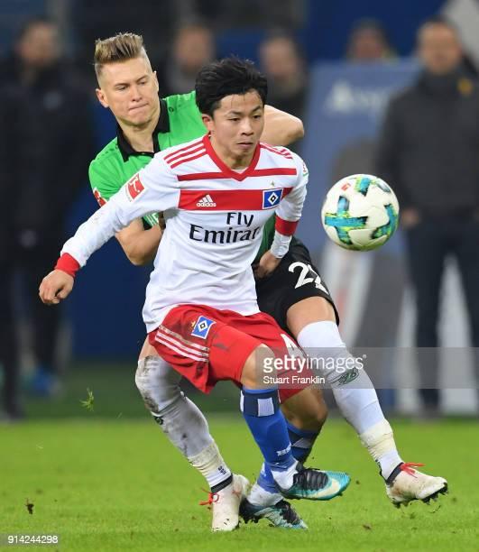 Tatsuya Ito of Hamburg is challenged by Matthias Ostrzolek of Hannover during the Bundesliga match between Hamburger SV and Hannover 96 at...