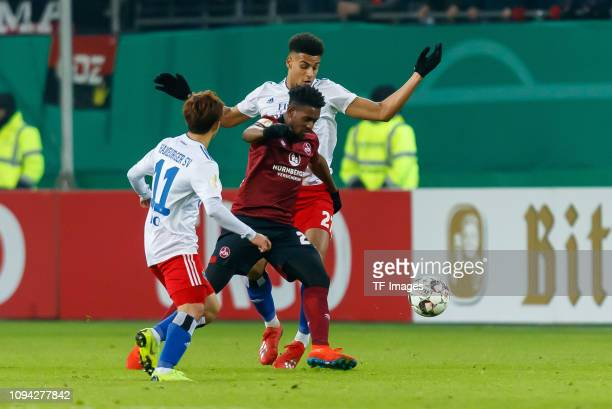 Tatsuya Ito of Hamburger SV Virgil Misidjan of 1 FC Nuernberg and Josha Vagnoman of Hamburger SV battle for the ball during the DFB Cup match between...